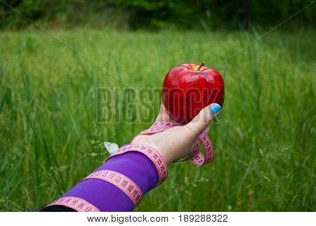 Lose weight fat woman close-up of the right hand holds a large red apple white blue butterfly sits on the hand short nails blue on a background of green grass blurred background pink measuring tape wound on the hand side view