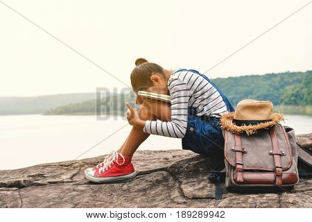 Happy Asian girl reading a book in nature background Relax time on holiday color of vintage tone and soft focus