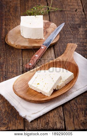 Sliced fresh brined white cheese from cow milk on wooden table