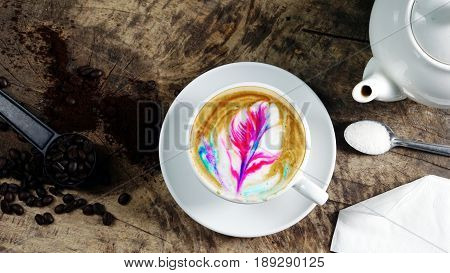 Hot rainbow cappuccino or latte art coffee. A cup of coffee on the wooden table with dark roasted coffee beans. Morning breakfast with coffee. Latte art created by pouring steamed milk.