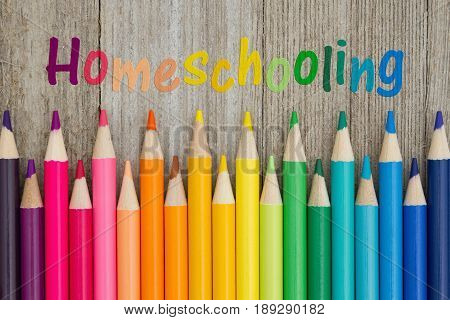 Homeschooling text with colorful pencil crayons on a weathered wood