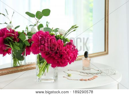 Beautiful bouquet with fragrant peonies on dressing table near mirror