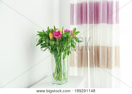 Glass vase with bouquet of beautiful tulips on chest of drawers