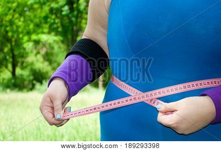 Fat woman wants to lose weight diet side view in blue suit on green grass bush tree hands abdomen torso torso chest location on the right purple black pink measuring tape figures keeps measuring volume in hands with short blue nails on blurred background