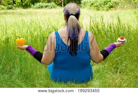 Fat woman wants to lose weight diet view from behind sits on grass image man figure in blue suit bush tree holds in hands choice in left hand yellow sweet bell pepper in right hand cake, torso purple black short nails blue on blurred background fat sport