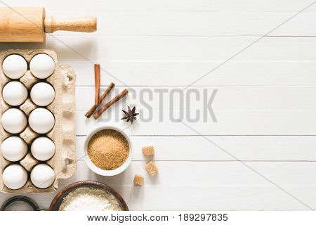 Baking ingredients on white wood with copy space. Eggs, brown sugar, white flour, spices and rolling pin on white wooden background. Top table top view. Cooking, baking background, recipe mock up
