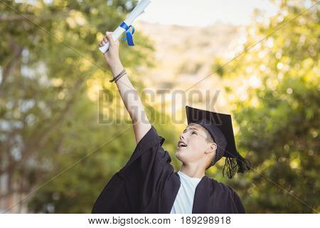 Excited graduate schoolboy with degree scroll in campus at school
