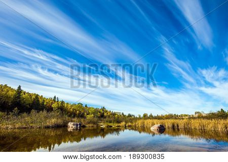 Indian summer in Manitoba, Canada. Cirrus clouds are reflected in the Winnipeg River. Old Pinawa Dam Park. The concept of ecological and recreational tourism