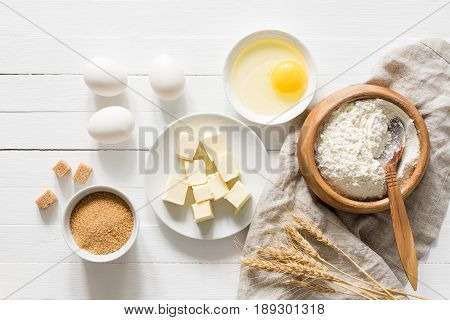 Baking bread or baking cake ingredients. Cubed butter, brown sugar, eggs and white flour on white wooden table. Rustic style baking / cooking ingredients. Top view