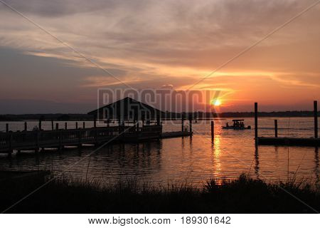 sunset across intracoastal waterway with reflections and boat ramp