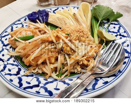 Close-up Pad Thai Serves on Dish with Fork and Spoon