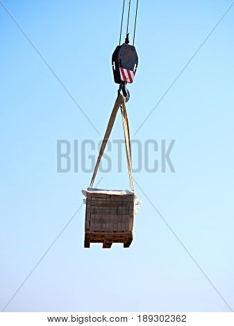Crane Hook With Stacked White Bricks On A Wooden Pallet, Clear Blue Sky In The Background