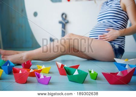 pregnant woman with a big belly is behind the colored boats