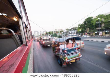 Blur Tuk Tuk in Bangkok take pictures from the buses in traffic jam. Auto rickshaw.