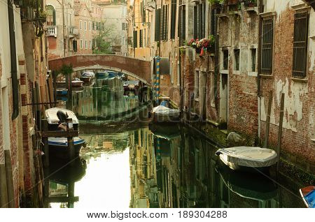 Classical picture of the venetian canals with gondola across the canal.