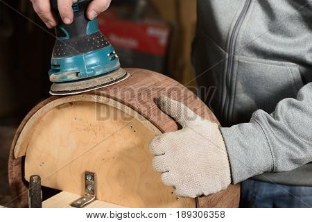 Carpenter grinding handmade wooden drum with sandpaper closeup
