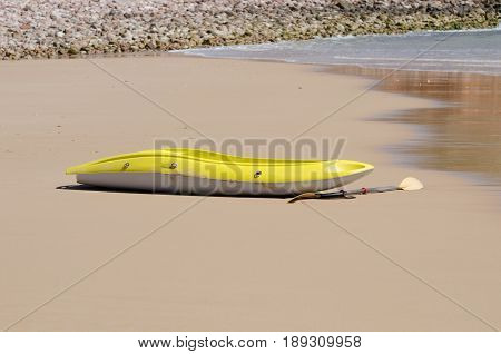 Yellow canoe lying on the beach with no one around.