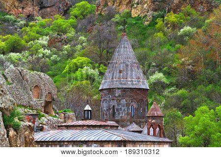 Architecture among green trees. Christian temple monastery GEGHARD (Armenia)