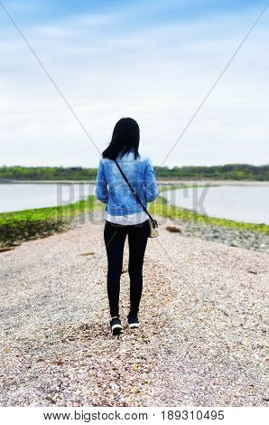 A chinese woman walking on a sandbar at lowtide from charles island to silver sands state park in Milford connecticut.