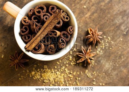 Cinnamon and anise sticksin cup on textured background.overhead view. Cinnamon