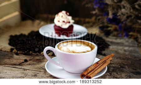 A cup of latte or cappuccino coffee with milk on a wood table with roasting coffee beans and the red velvet cake. Aroma and flavor coffee beverage. Morning breakfast with coffee. Latte art created by pouring steamed milk.