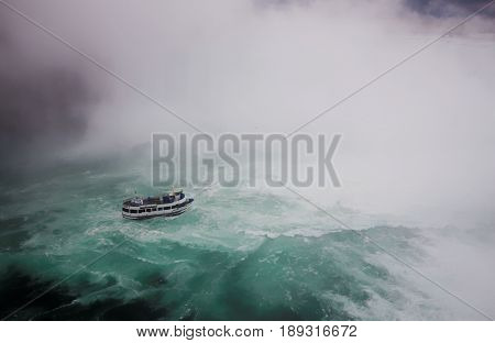 Niagara Falls, USA/Canada, 19 April 2017; Editorial photograph of Maid of the Mist tourist boat approaching Horseshoe (Canadian) Falls in stormy weather