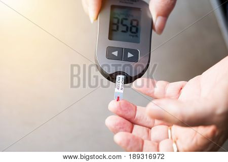 old women checks the amount of sugar in the blood. High blood sugar lever.