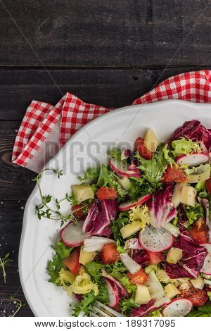 Fresh salad with mixed greens radish cheese and tomato in a plate on wooden background. Italian Mediterranean or Greek cuisine. Vegetarian vegan food