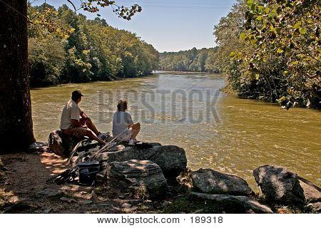 Couple Sitting Along River