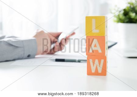 Law Word From Toy Blocks. Lawyer Working In Background