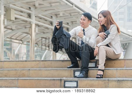 Two businessmen sitting at stair and take self ie with a smart phone in hand on modern city.