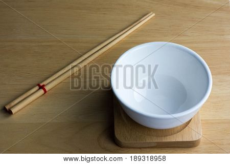 Empty ceramic white bowl isolated on the wood ground
