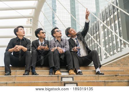 Asian businessman middle-aged pointing upward. let the young businessman see something in modern city.