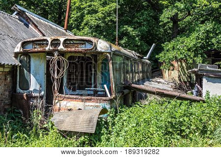 Abandoned house made of rusty old Soviet bus. Green post apocalypse concept