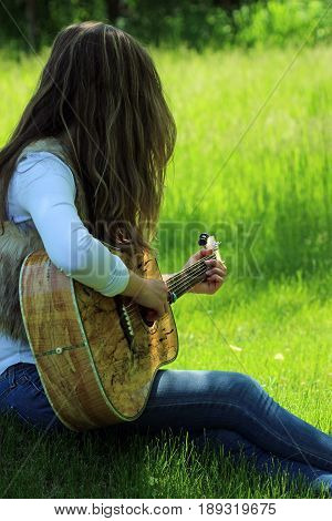 Bohemian dressed female strums acoustic guitar in the grass