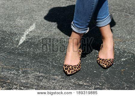 Female wearing leopard print high heels with legs crossed on blacktop