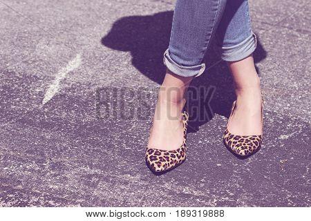 Female wearing leopard print high heels on blacktop