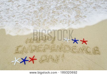 Independence USA background with white red and blue starfishes on the sandy beach near ocean