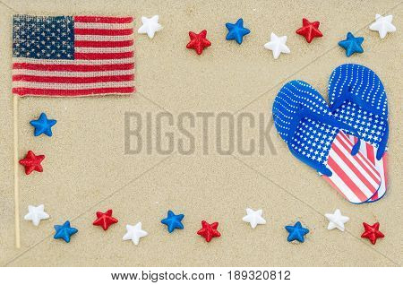 Patriotic USA background with flip flops and American flag on the sandy beach