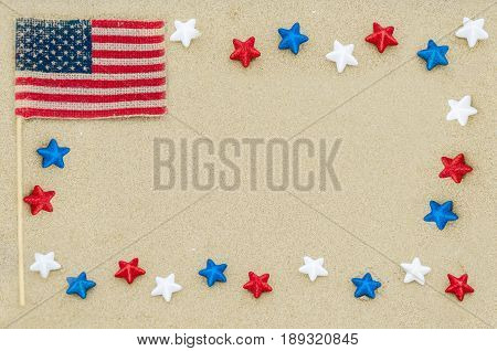 Patriotic USA background with white blue and red stars and American flag on the sandy beach