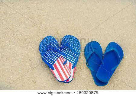 Patriotic USA background with flip flops on the sandy beach