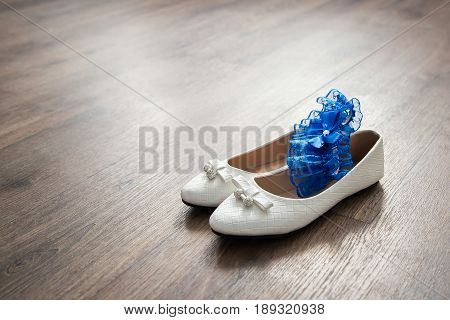 White shoes without heels and a blue garter the bride on a wooden floor