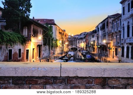 night landscape with the image of  channel in Venice, Italy with bridge parapet under the frontground. Focus is under the parapet