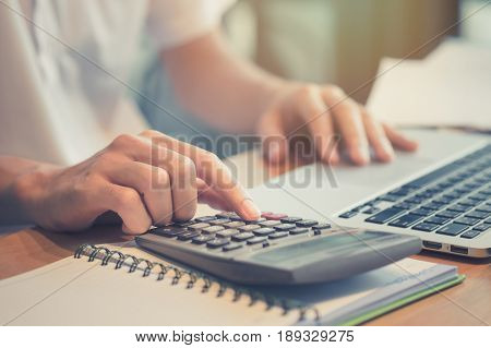 Close Up Business Man Using Calculator And Laptop Computer For Calculating With Finance Paper, Tax,