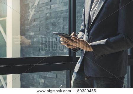 Business Man Stand Beside Window In Office And Holding Tablet Using Calculator For Do Math Of Financ
