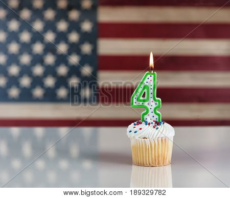 Vanilla cupcake and number four candle with rustic wooden United States Flag in background. July 4th holiday concept