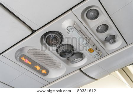 Adjustable ights and air conditioners overhead seat controls of a commercial aircraft in an airplane with no-smoking and seat belt on signs