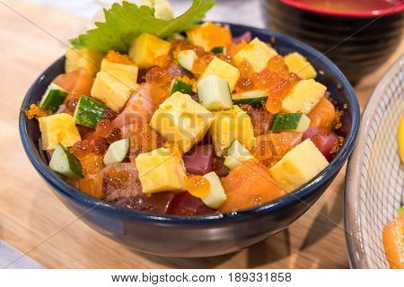 Bowl of mixed raw fish on rice with egg and vegetable on wooden table.