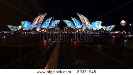 Sydney Australia - May 30 2017. Sydney Opera House and glass reflections at the end of the pier. Opera House illuminated with colourful light design imagery during the Sydney Vivid show.