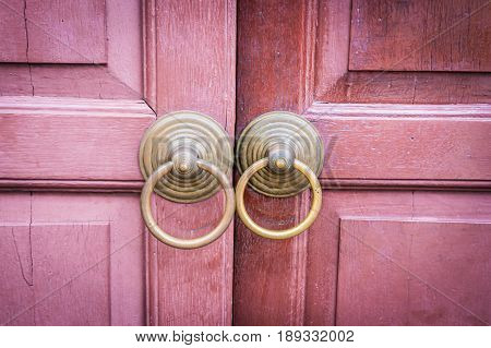 traditional metal open door on a retro wooden door is unlock.